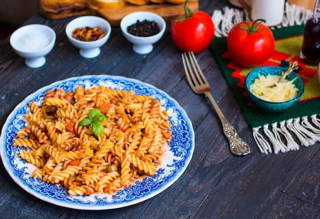 Makaron fusilli z sosem pomidorowym, pomidorami, cebulą, czosnkiem, suszoną papryką, oliwkami, pieprzem i oliwą z oliwek