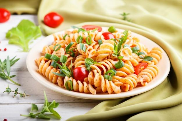 Makaron fusilli z sosem pomidorowym pomidory czereśniowe sałata i zioła na białym tle drewnianych