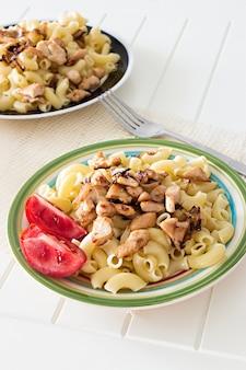 Makaron gomiti ze smażonym kurczakiem i kawałkami cebuli z pomidorem i widelcem.