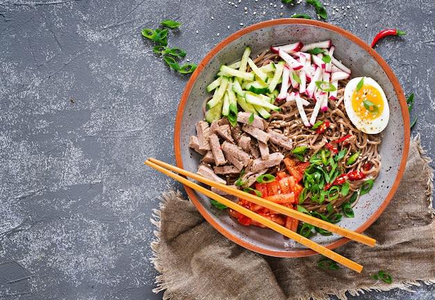 Makaron gryczany z wołowiną, jajkami i warzywami. koreańskie jedzenie. zupa z makaronu gryki. widok z góry. leżał płasko