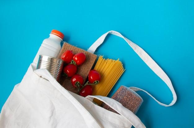 Makaron gulasz pomidory kasza gryczana mleko niezbędne podczas kwarantanny kawid-19 w białej torebce lnu