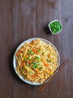 Makaron hakka to popularne indochińskie przepisy kulinarne. makaron schezwan z warzywami w talerzu. widok z góry.