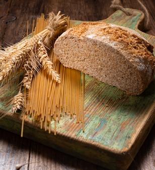 Makaron i chleb razowy z kłosami pszenicy na rustykalnym drewnianym stole
