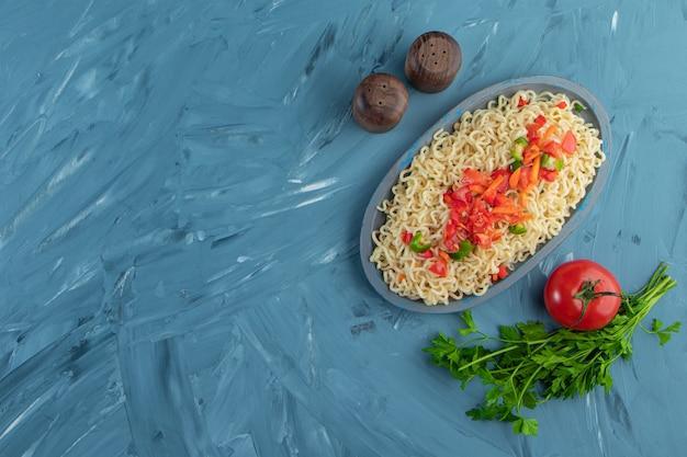 Makaron i sałatka na drewnianym talerzu obok pietruszki i pomidorów, na tle marmuru.