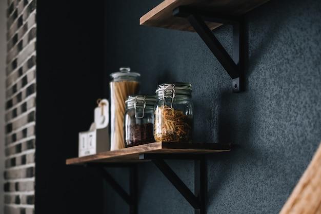 Makaron i sklep spożywczy w szklanych słoikach na drewnianej półce w kuchni.