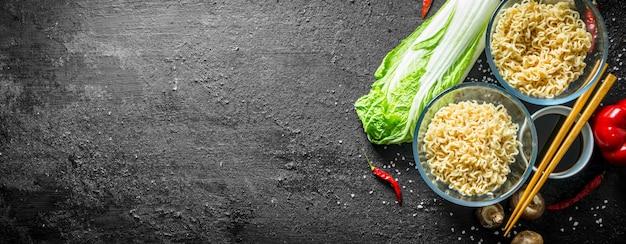 Makaron instant w miseczkach z grzybami, kapustą pekińską i sosem sojowym na czarnym rustykalnym stole