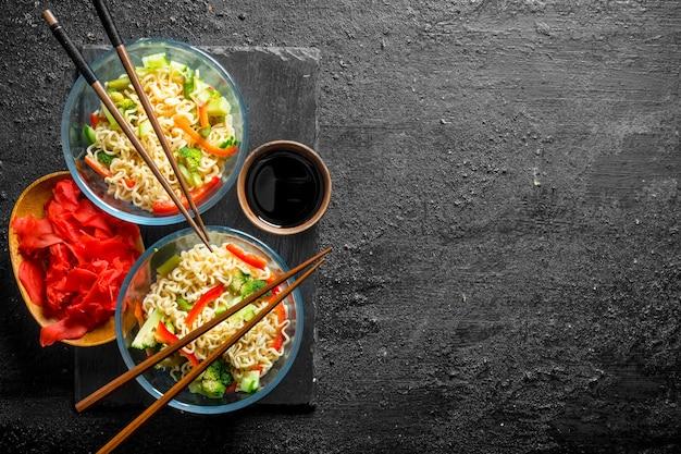Makaron instant w miseczkach z warzywami, imbirem i sosem sojowym.