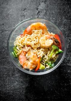 Makaron instant w szklanej misce z krewetkami i warzywami. na ciemnym tle rustykalnym