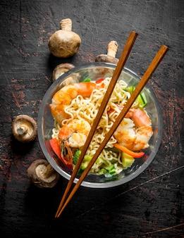 Makaron instant w szklanej misce z krewetkami, warzywami i grzybami.