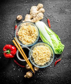 Makaron instant z imbirem, grzybami, papryką, kapustą pekińską i sosem sojowym. na czarnym tle rustykalnym