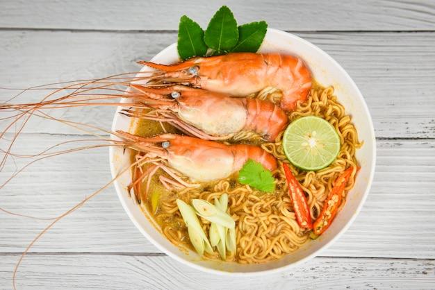 Makaron instant z krewetkami, pikantną miską do zupy, limonką / gotowane owoce morza ze stołem i zupą z krewetek składniki i przyprawy tajskie jedzenie azjatyckie tradycyjne, tom yum kung
