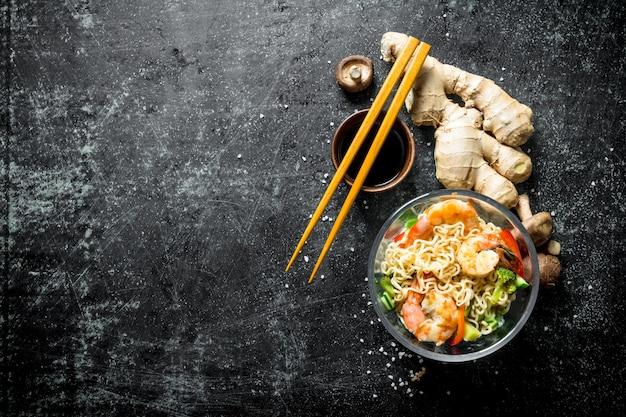 Makaron instant z krewetkami, świeżym imbirem, grzybami i sosem sojowym. na ciemnym tle rustykalnym
