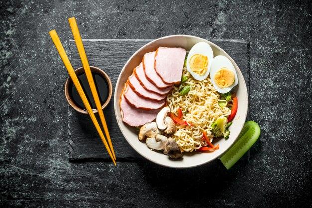 Makaron instant z szynką, warzywami, jajkiem i sosem sojowym na kamiennej desce.