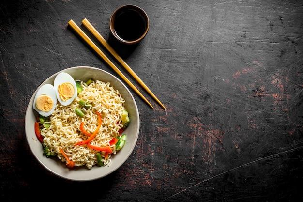Makaron instant z warzywami i pokrojonym w plasterki jajkiem. na ciemnym tle rustykalnym