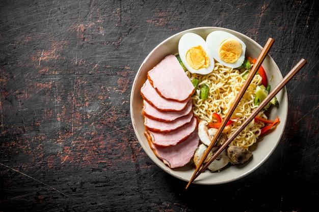 Makaron instant z warzywami, jajkiem, pieczarkami i plastrami boczku.