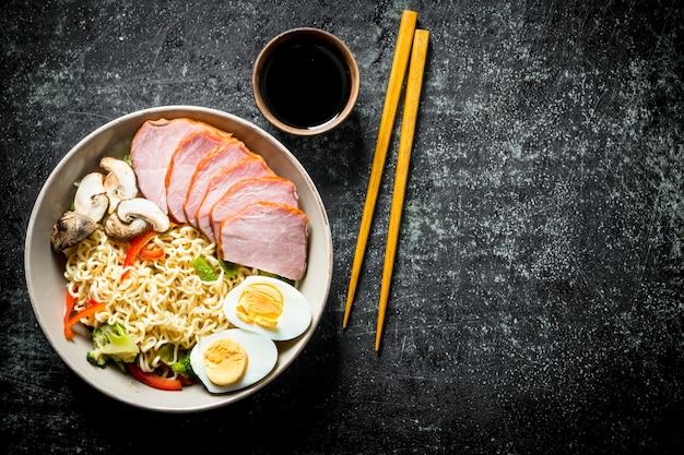 Makaron instant z warzywami, jajkiem, szynką, sosem sojowym i pałeczkami. na ciemnym tle rustykalnym
