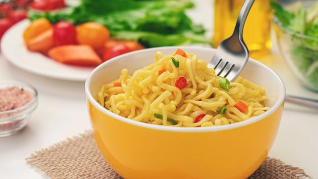 Makaron instant z widelcem, podawany z warzywami i ziołami, pikantny azjatycki obiad