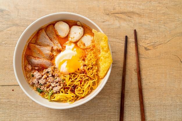 Makaron jajeczny z wieprzowiną i klopsikiem w ostre zupie lub tom yum noodles po azjatyckim stylu