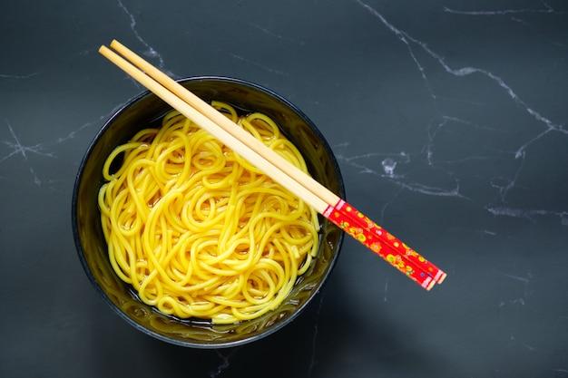 Makaron jest w misce umieszczonej na stole. żółty makaron w czarnej misce z miejscem na kopię.