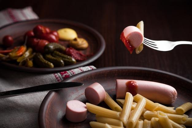 Makaron kiełbasowy z sosem i pikantnymi przystawkami.