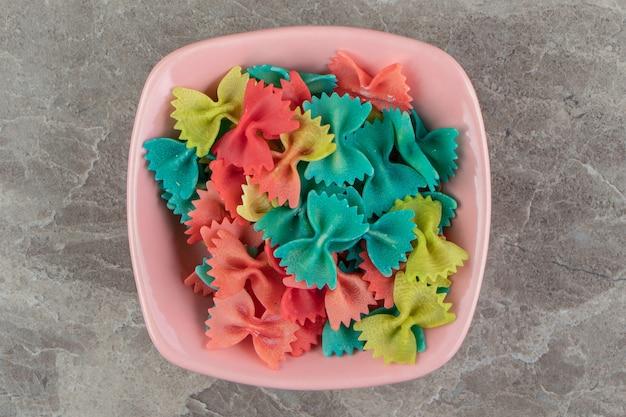 Makaron kolorowe wstążki w misce różowy.