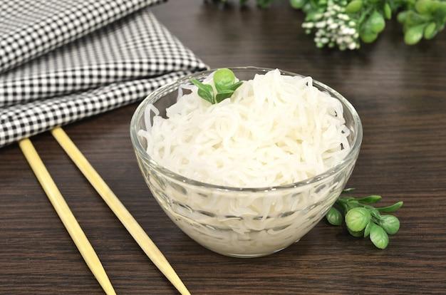 Makaron konjac lub shirataki z chińskimi pałeczkami. japońskie tradycyjne danie. zdrowa żywność dla utraty wagi, koncepcja diety ketonowej.