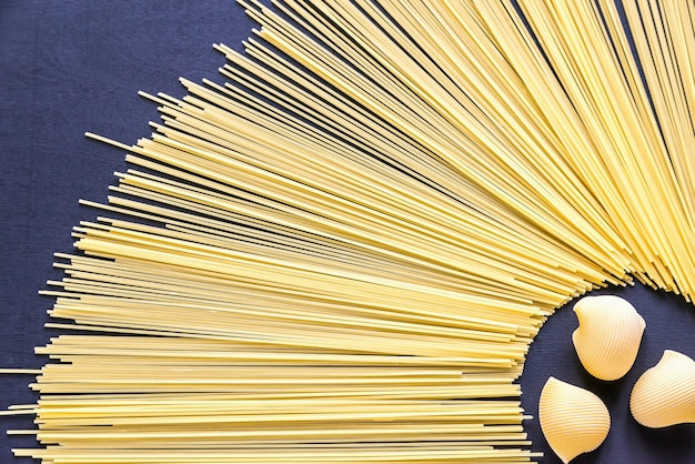 Makaron lumaconi i spaghetti na ciemnym tle