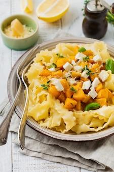 Makaron mafaldine napoletane z pieczoną dynią, serem feta i ziołami przyprawowymi w talerzu ceramicznym na białym drewnianym stole. styl rustykalny. widok z góry.