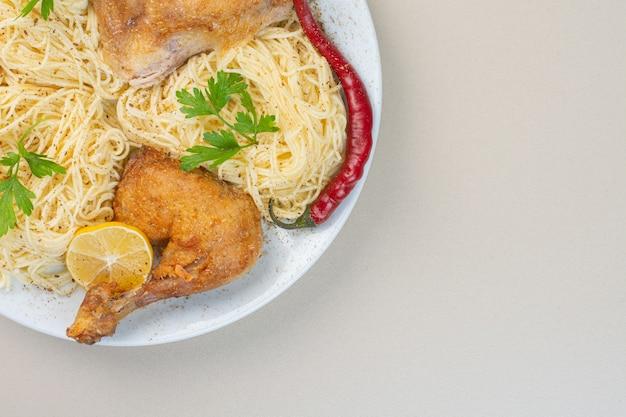 Makaron, mięso z kurczaka, papryka i cytryna na talerzu, na marmurowej powierzchni