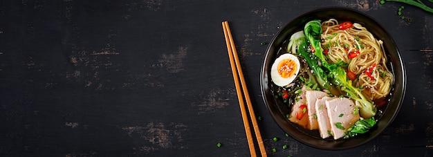 Makaron miso z jajkiem, wieprzowiną i kapustą pak choi w misce na ciemnym stole