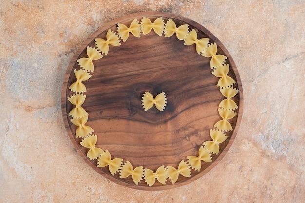 Makaron muszka na drewnianym talerzu na marmurowej przestrzeni.