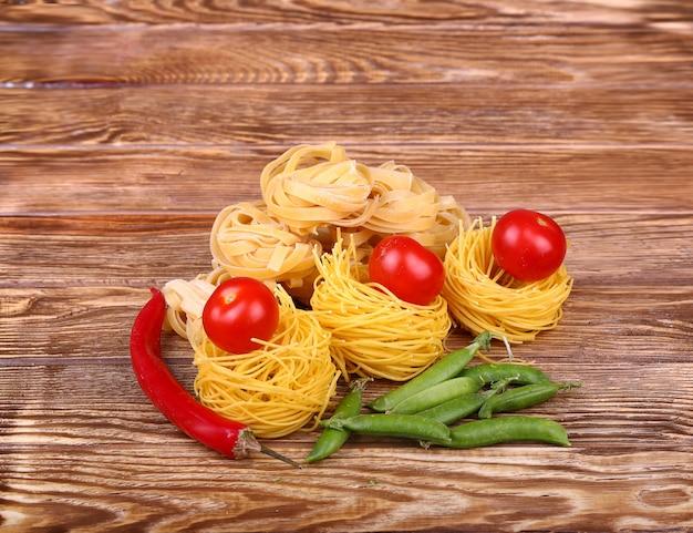 Makaron na drewnianej ścianie z pomidorem, sałatą pieprzową i pieprzem