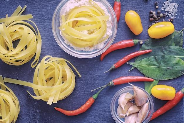 Makaron na stole z przyprawami i warzywami. makaron z warzywami do gotowania na czarnym tle kamienia.