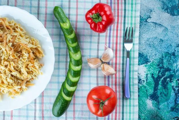 Makaron na talerzu obok różnych warzyw i widelec na ściereczce, na niebieskim stole.