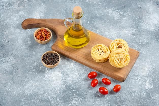 Makaron, oliwa z oliwek, przyprawy i pomidory na desce.