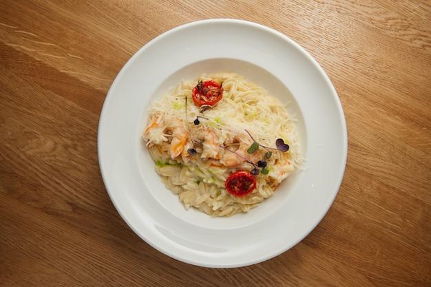 Makaron orzo z krewetkami, parmezanem i sosem na białym talerzu. widok z góry