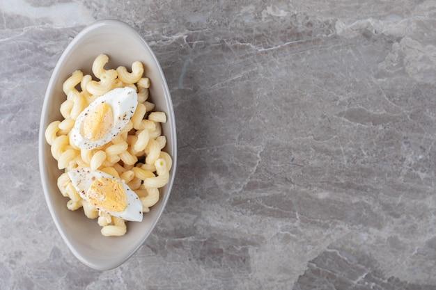 Makaron ozdobiony gotowanym jajkiem w ceramicznej misce.