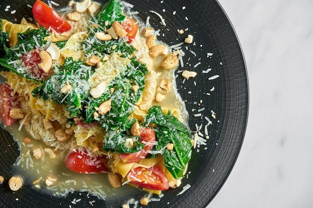 Makaron pappardelle z pasternakiem, sosem śmietanowym, blanszowaną zieleniną, pomidorami i orzechami na czarnym talerzu na białym marmurze