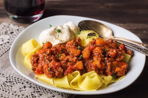 Makaron pappardelle z ragoutem mięsnym i serem burrata na rustykalnym drewnianym tle. kuchnia włoska. selektywna ostrość.