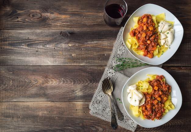 Makaron pappardelle z ragoutem mięsnym z dynią i serem burrata na rustykalnym drewnianym tle. kuchnia włoska. widok z góry. skopiuj obszar przestrzeni.