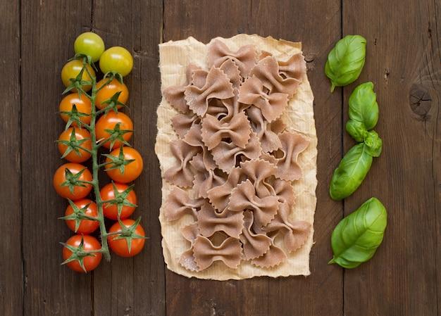 Makaron pełnoziarnisty, pomidory i bazylia na drewnie