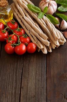 Makaron pełnoziarnisty, warzywa, bazylia i oliwa z oliwek na tle drewnianych