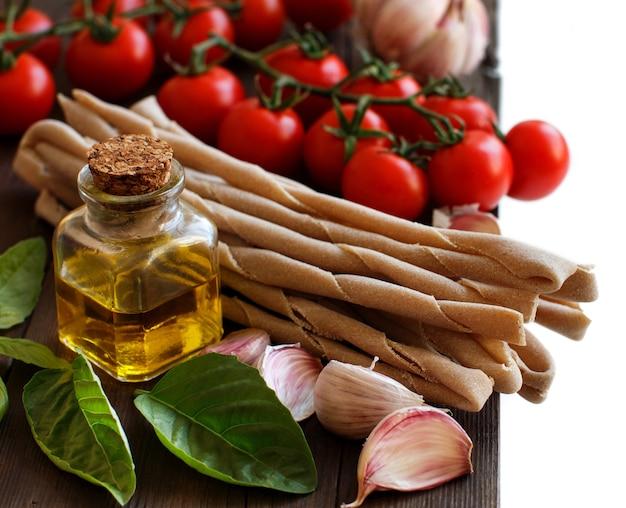 Makaron pełnoziarnisty, warzywa, zioła i oliwa z oliwek na drewnianym stole