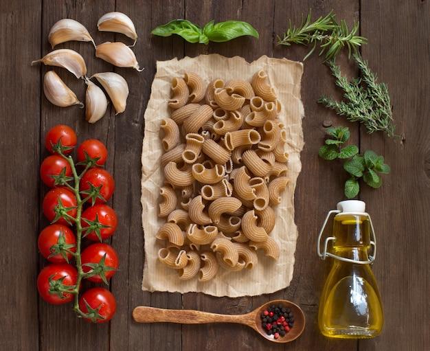 Makaron pełnoziarnisty, warzywa, zioła i oliwa z oliwek na drewno widok z góry