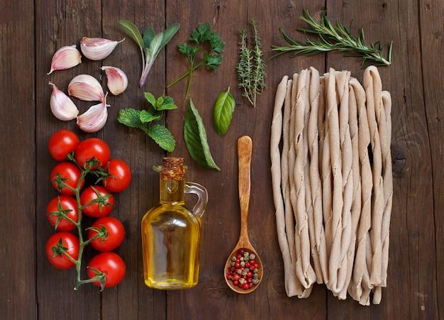 Makaron pełnoziarnisty, warzywa, zioła i oliwa z oliwek na podłoże drewniane