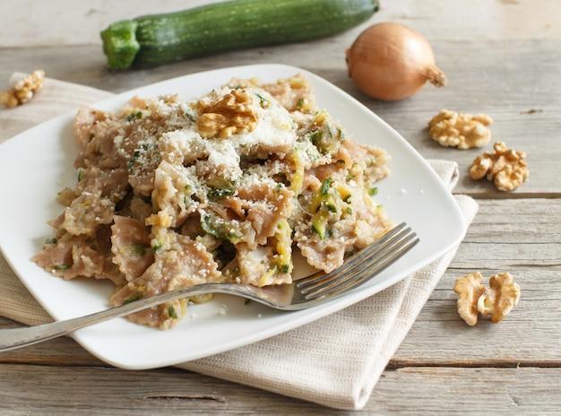 Makaron pełnoziarnisty z kremem topinambur, orzechami włoskimi i cukinią na drewnie z bliska