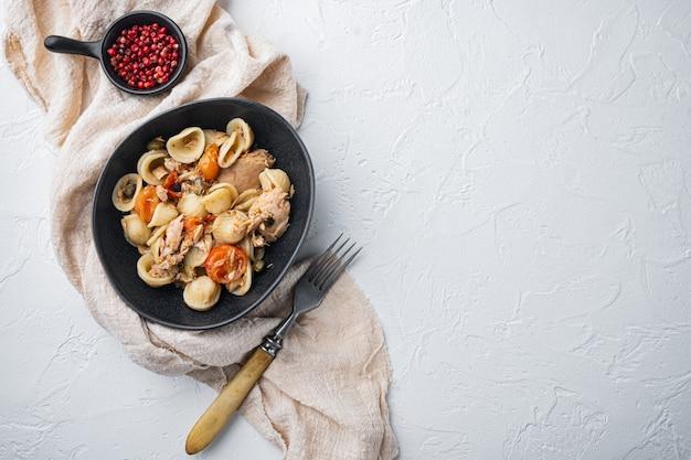 Makaron pełnoziarnisty z suszonymi pomidorami i tuńczykiem w misce na biały, widok z góry