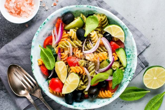 Makaron pełnoziarnisty z warzywami na białym talerzu na jasnoszarym tle łupkowym, kamiennym lub betonowym. widok z góry z miejsca na kopię.