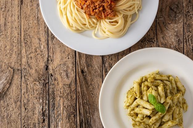 Makaron penne i spaghetti z potrawami z sosem bolońskim na drewnianym stole