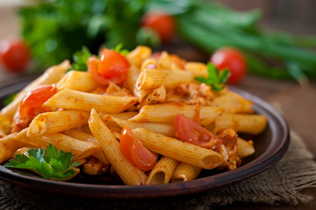 Makaron penne w sosie pomidorowym z kurczakiem i pomidorami na drewnianym stole